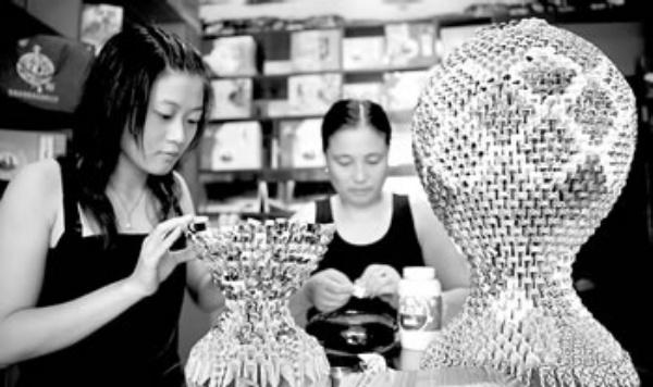 今夏以来,一种新型民间手工艺品制作在华蓥市悄然流行。市民利用废弃的扑克牌、香烟盒,折叠成精美的工艺品,变废为宝,美化了生活。图为9月1日,四川华蓥市民利用废纸制作花瓶等工艺品。 邱海鹰摄(中经网供图)