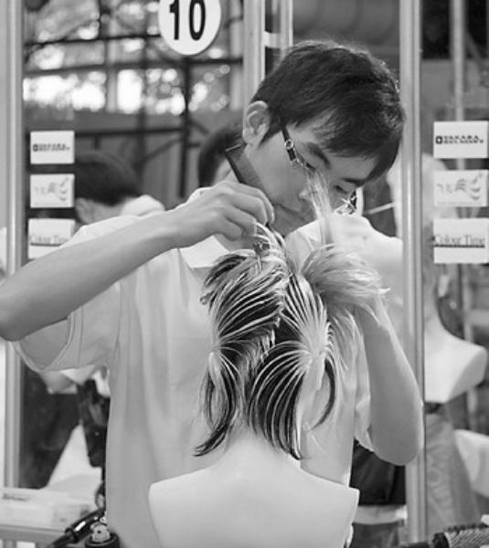 巴黎汇发型艺术公司的展台前,几位发型师正在现场演示发型制作,引来了图片