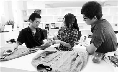 图为雅戈尔品牌工作室的设计师在商讨设计方案. 资料图片