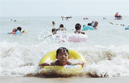 ▼江苏连云港市连岛海滨浴场游客戏水消暑.